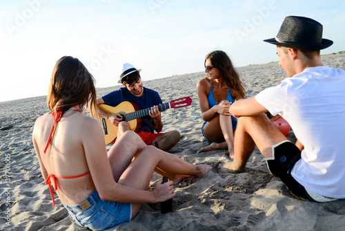 group of young people man and woman playing guitar singing having fun and party on beach at summer sunset holiday vacation