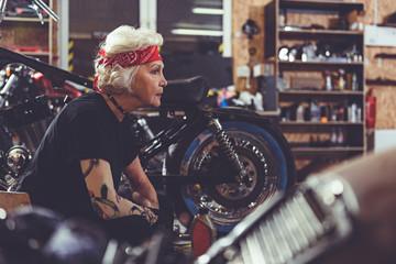 Thoughtful pensioner making machine maintenance in garage