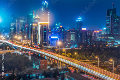 In de dag Tunnel light trails on city street with cityscape at night in China.