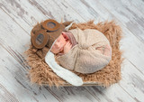 funny sleeping wrapped newborn with pilot hat, top view