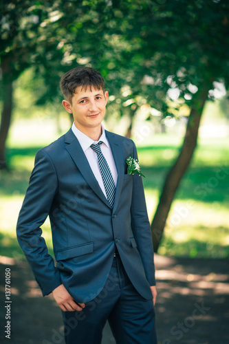 portrait of a young groom standing near park