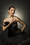 Beautiful expressive ballerina in the role of a black swan, wearing black tutu on dark background
