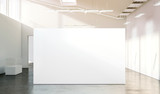 Blank white wall mockup in sunny modern empty gallery, 3d rendering. Clear big stand mock up in museum with contemporary art exhibitions. Large hall interior with wide banner exposition template. - 137764645