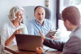 Fototapety Positive aged couple consulting with insurance agent