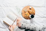 Top view of woman reading a book in bed and having breakfast