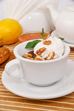 Hot chocolate with whipped cream and walnuts, decorated with mint leaves in a white cup on a decorative tablecloth
