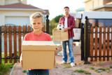 Portrait of cute young boy standing in driveway holding big cardboard box and looking at camera, with his father taking more boxes out from van in background