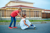 Portrait of boy and girl playing in the street: boy pushing her sister sitting on skateboard in middle of road in quiet town neighborhood