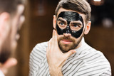 Young man with facial mask looking in mirror