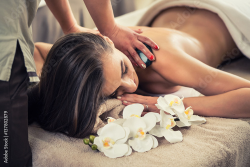 Woman enjoying the therapeutic effects of a traditional hot stone massage