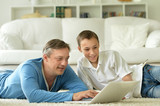 son and father using laptop