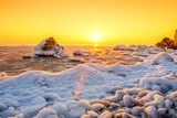 sunrise on the bank of the winter sea. The ice floes floating in the water, frozen water, the sun rising over the horizon.
