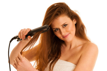 Beautiful young woman with long hair using hair straighteners isolated on white