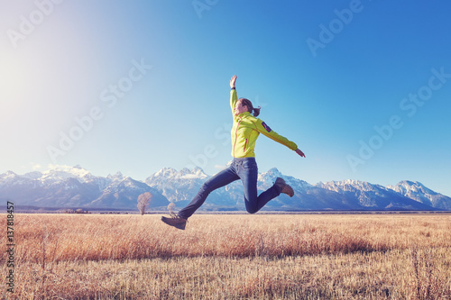 Póster Happy young woman jumping on a meadow at sunset, color toned image, Grand Teton mountain range in distance, Wyoming, USA