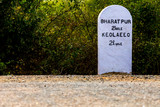 Milestone with distance marking on path with bushes in background in Keoladeo National Park, Bharatpur a bird century