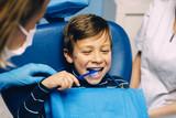 Doctor dentist teaching a child to brush teeth.