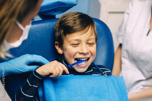 Doctor dentist teaching a child to brush teeth. - 137845638