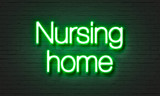 Nursing home neon sign on brick wall background.