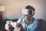Concept of technology,gaming,entertainment and people.African man playing virtual reality glasses video game while relaxing in living room at home.Selective focus on VR headset.Blurred background.