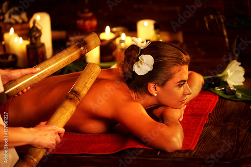 Bamboo massage of woman in spa salon. Girl on candles background in massage spa salon. Luxary interior in oriental therapy salon. Female have relax big stick after sport on red towel. Close up of