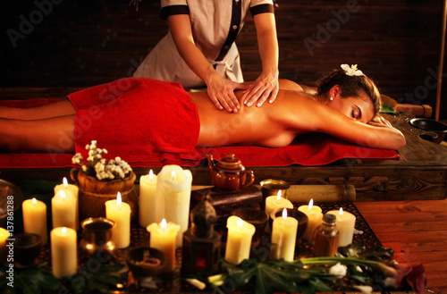 Massage of woman in spa salon. Girl on candles background treats problem back spa salon. Luxary interior with working masseuse in oriental therapy salon. Female bare back with smooth skin have relax .