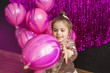 Pretty little girl holds pink balloon at hands
