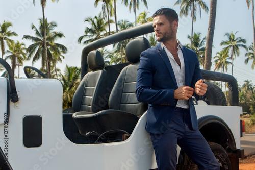 Plakát Handsome man near the car in suite