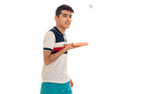 a young guy in a bright t-shirt stands sideways and holding a tennis racket isolated on white background