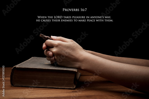 Poster hands holding a cross on holy Bible with verse