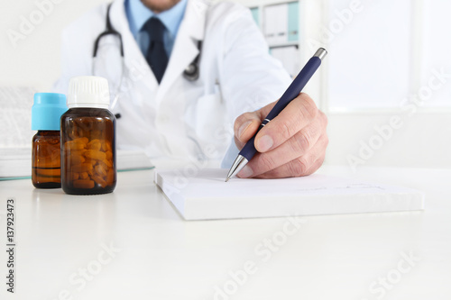 doctor writing RX prescription in medical office with drugs on desk