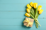 Fototapety Yellow tulips and gift box on blue wooden background