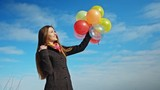 Woman attractive joyful girl playing with colorful balloons. Spring holidays, celebration and lifestyle concept.