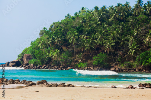 Empty beach with palms on a mountain in hot season