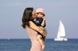 Quadro Eine junge Mutter mit ihrem Baby am Strand