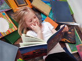 child and a lot of books around. Little girl reading a book lying on the floor - 137966804