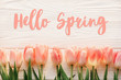 hello spring text sign, beautiful pink tulips on white rustic wooden background flat lay. flowers in soft morning sunlight with space for text. greeting card concept