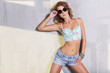 Beautiful brunette woman in summer outfit: blue shorts and top, and keds, with sunglassess. in sexy fashion poses. indoor. studio