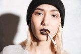 Portrait of beautiful young woman hipster in hat smoking cigarette