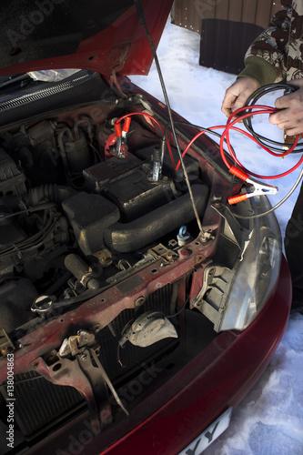 Poster Mechanik podłącza kable rozruchowe do rozładowanego akumulatora