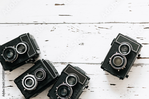 Poster collection old  vintage retro photo cameras on white wooden background