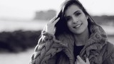 Beautiful woman with long hair smiling looking camera in front of the ocean black and white slow motion