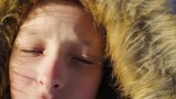 Portrait of a teenage boy close up. The boy corrected hood. Sunny winter evening in the forest. Strong wind.