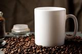 White coffee mug with coffee beans and glass jar with ground coffee inside