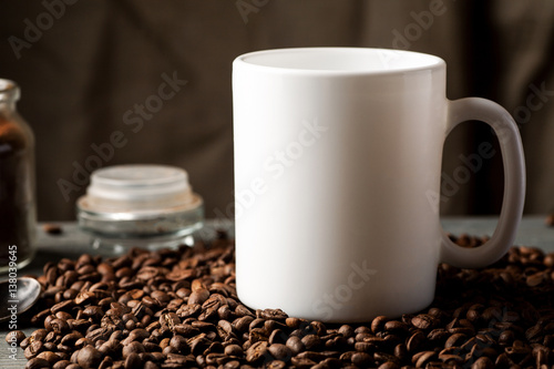 Foto op Aluminium Koffiebonen White coffee mug with coffee beans and glass jar with ground coffee inside