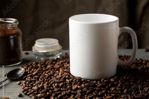 Fotobehang Koffiebonen White coffee mug with coffee beans and glass jar with ground coffee inside.