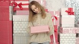 Beautiful Girl in a Sweater Among the Boxes With Gifts