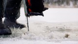 close up view of fisherman hands holding chainsaw which cut ice of frozen lake to make a hole and makes streams of cold water during winter day