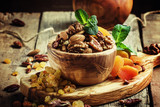 Raisins, dried apricots and assorted nut in a wooden bowl, selective focus