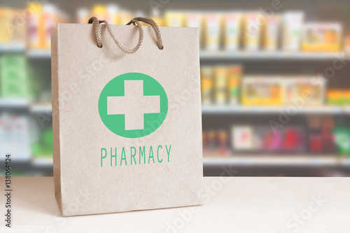 Aluminium Apotheek Recycled paper bag with a green Pharmacy logo in a drugstore. Empty copy space for Editor's content.