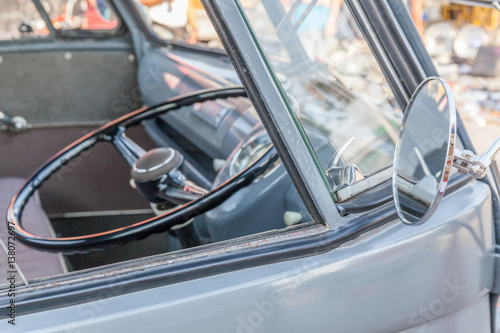 Shiny retro wing mirror of classic beetle grey Volkswagen and blurred background of steering wheel inside Poster